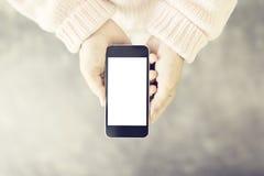 Telefono cellulare in bianco nelle mani delle donne Immagini Stock
