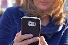 Telefono cellulare caucasico della tenuta della donna e esaminarlo Fotografie Stock Libere da Diritti