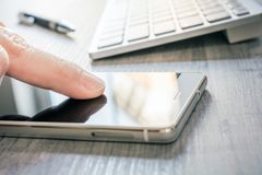 Telefono cellulare commovente del dito con la riflessione accanto ad una tastiera bianca e ad un biro su una Tabella - concetto d immagini stock libere da diritti