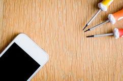Telefono cellulare con gli strumenti di riparazione e dello schermo in bianco su fondo di legno fotografia stock