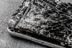 Telefono cellulare con lo schermo attivabile al tatto rotto su fondo grigio fotografia stock libera da diritti