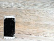 Telefono cellulare con lo schermo rotto ed il fondo vuoto immagine stock libera da diritti