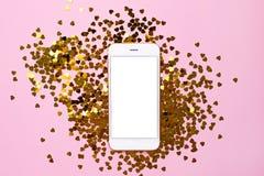 Telefono cellulare con lo schermo vuoto bianco sul fondo rosa della carta di colore con i coriandoli dorati del cuore fotografie stock libere da diritti