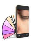 Telefono cellulare con un insieme di trucco Fotografie Stock Libere da Diritti