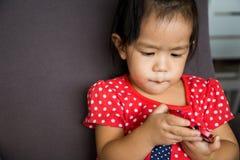 Telefono cellulare del gioco della ragazza con emozione seria Immagine Stock Libera da Diritti