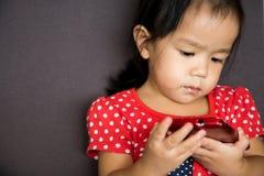 Telefono cellulare del gioco della ragazza con emozione seria Immagini Stock Libere da Diritti