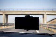 Telefono cellulare della tenuta dell'automobile con lo schermo nero in automobile Ponte a fondo Immagine Stock Libera da Diritti
