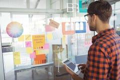 Telefono cellulare della tenuta dell'uomo d'affari mentre esaminando le note adesive in ufficio Immagini Stock Libere da Diritti