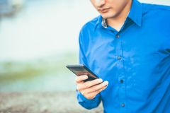 Telefono cellulare della tenuta dell'uomo d'affari per il messaggio, il email ed il funzionamento del controllo immagine stock libera da diritti