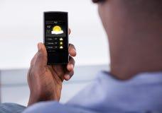 Telefono cellulare della tenuta della persona Immagine Stock