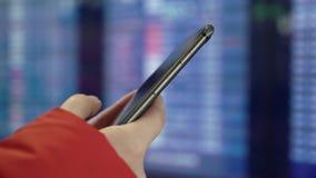 Telefono cellulare della tenuta della donna ed esaminare il bordo di informazioni in aeroporto stock footage