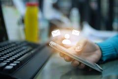 Telefono cellulare della tenuta della mano della donna con il email e l'icona umana fotografia stock