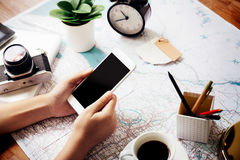 Telefono cellulare della tenuta sulla mappa per preparare viaggio Immagini Stock