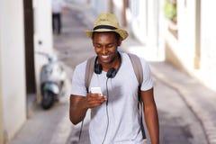 Telefono cellulare di camminata del giovane uomo afroamericano felice Fotografia Stock