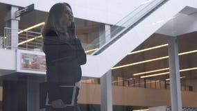 Telefono cellulare di conversazione della donna di affari nell'edificio per uffici moderno archivi video