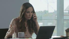 Telefono cellulare di conversazione della donna nervosa nel luogo di lavoro Telefono di conversazione delle free lance arrabbiate archivi video