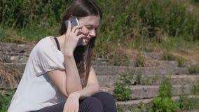 Telefono cellulare di conversazione della giovane donna che si siede nel parco video d archivio