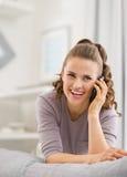 Telefono cellulare di conversazione della giovane donna felice in salone Immagini Stock