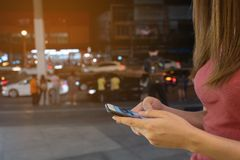 Telefono cellulare di uso della donna, notte nella citt? fotografia stock libera da diritti