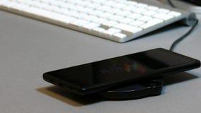Telefono cellulare disposto sul carico senza fili del caricatore del telefono stock footage