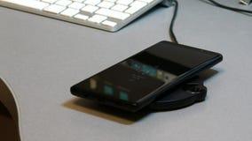 Telefono cellulare disposto sul carico senza fili del caricatore del telefono archivi video