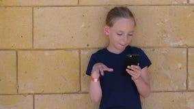 Telefono cellulare e condizione adorabili di lettura rapida della ragazza vicino alla parete di pietra gialla video d archivio