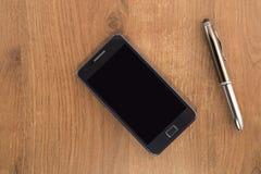 Telefono cellulare e la penna fotografia stock