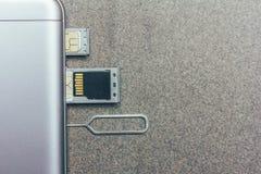 Telefono cellulare e scanalature aperte per le carte SIM nane, il micro azionamento di deviazione standard e la chiave del metall immagine stock libera da diritti
