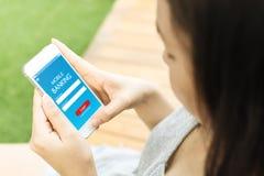 Telefono cellulare femminile asiatico della tenuta della mano ed usando la calca di applicazione Fotografie Stock Libere da Diritti
