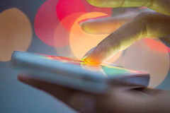 Telefono cellulare in mano di una donna, città di fondo leggero Fotografie Stock