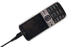 Telefono cellulare mentre facendo pagare fotografie stock