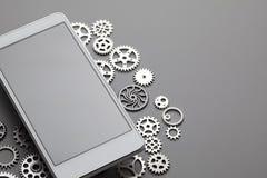 Telefono cellulare moderno bianco con lo schermo grigio in bianco ed i piccoli ingranaggi sulla tavola immagini stock libere da diritti