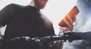 Telefono cellulare muscolare tatuato della tenuta del maschio nelle mani e nel per mezzo del app della mappa per la preparazione  fotografia stock