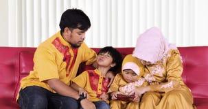 Telefono cellulare musulmano di uso della famiglia a casa video d archivio