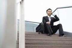 Telefono cellulare parlante bello dell'uomo di affari che si siede nella scala Immagine Stock