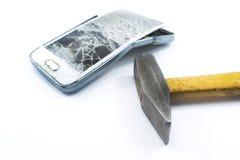 Telefono cellulare rotto con un martello su un fondo bianco fotografie stock