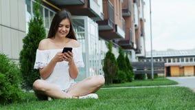 Telefono cellulare sveglio di uso della ragazza mentre sedendosi sull'erba vicino all'hotel, chiacchierante con gli amici archivi video