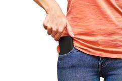 Telefono cellulare in una tasca delle blue jeans Isolato su priorità bassa bianca Immagine Stock