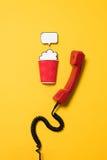 Telefono classico e tazza di carta con il fumetto isolato su giallo Immagini Stock Libere da Diritti
