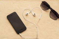 Telefono con le cuffie e gli occhiali da sole Immagini Stock Libere da Diritti