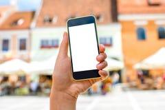 Telefono con lo schermo bianco sul fondo della città Fotografie Stock
