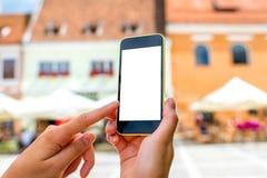 Telefono con lo schermo bianco sul fondo della città Immagine Stock