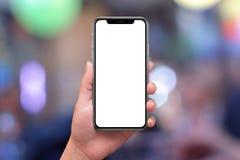 Telefono x con lo schermo curvo in mano della donna Luci e bokeh della città nel fondo immagine stock