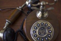 Telefono d'annata sulla tavola di legno con il microtelefono giù immagine stock