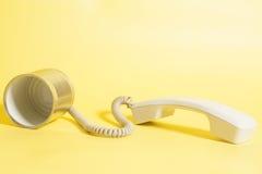 Telefono del barattolo di latta con il microtelefono su fondo giallo fotografia stock