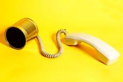 Telefono del barattolo di latta con il microtelefono su giallo fotografia stock