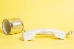 Telefono del barattolo di latta con il microtelefono su giallo immagini stock libere da diritti