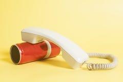 Telefono del barattolo di latta con il microtelefono su giallo fotografia stock libera da diritti