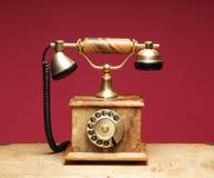 Telefono dell'annata e un vecchio su una priorità bassa rossa Fotografia Stock Libera da Diritti