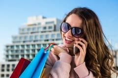 Telefono della ragazza durante l'acquisto Fotografie Stock Libere da Diritti
